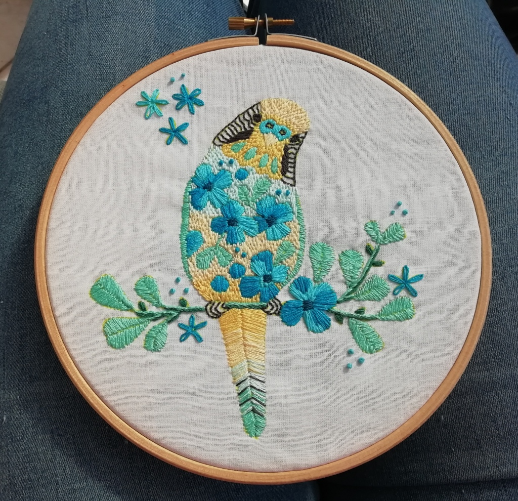 A hand-stitched picture of a yellow budgie on a spring branch, displayed in an embroidery hoop.