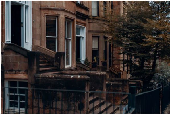 A photograph of a typical looking row of tenement houses in Glasgow: sandstone walls with many windows; front steps; railings; small trees.