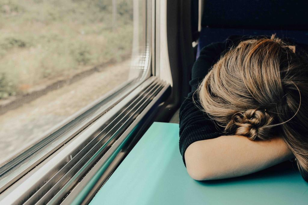 A young woman is hunched over a train table, resting her head on her arm, possibly asleep.