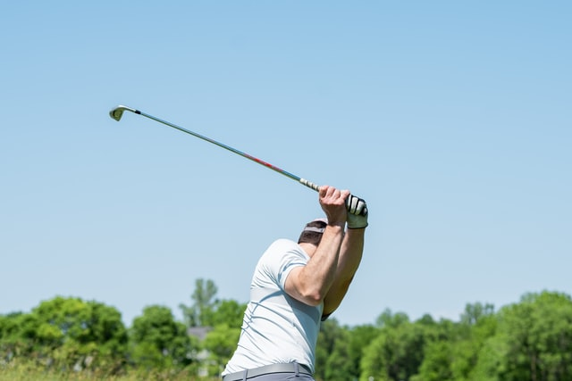 A man mid golf swing under a blue sky.