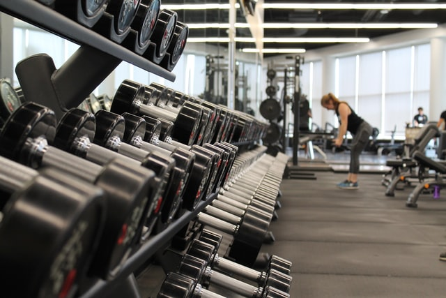 A view of a gym. Weights are in the foreground. A few people (exercising/standing) are visible in the background.
