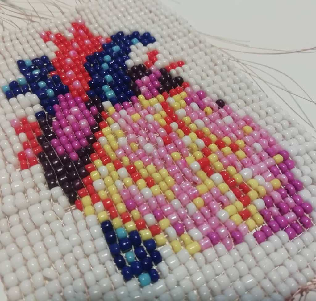 A close-up of a human heart made in beads. Some beads are misaligned and threads are visible. The colours are a bit off too.