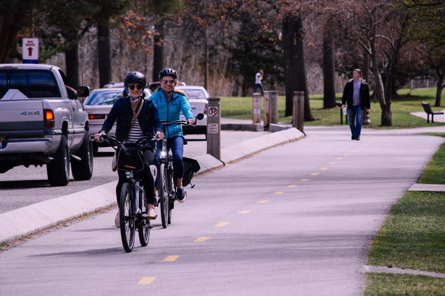 Two people cycling in a cycle lane. In the background is a park with people walking.
