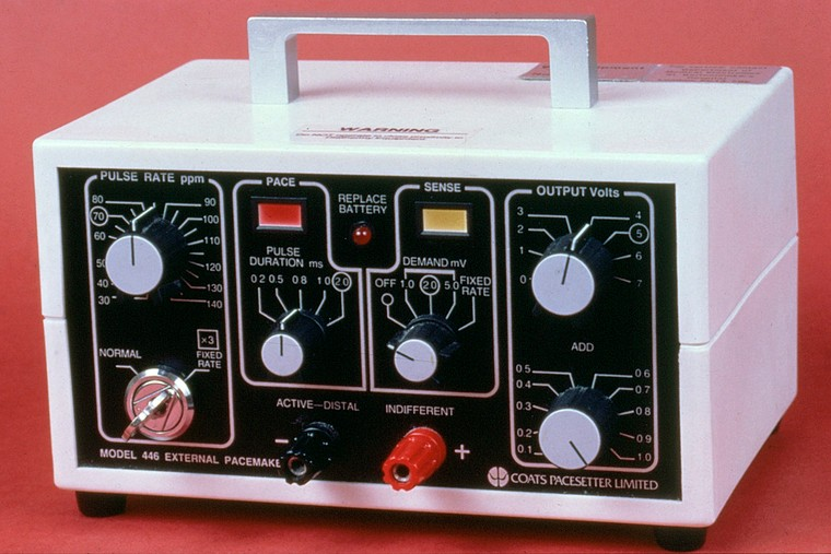 A white box with handle, covered in dials, lights and switches, labelled as (for example) pulse rate, pulse duration, output volts, replace battery, etc.  Company name: Coats Pacesetter Limited.