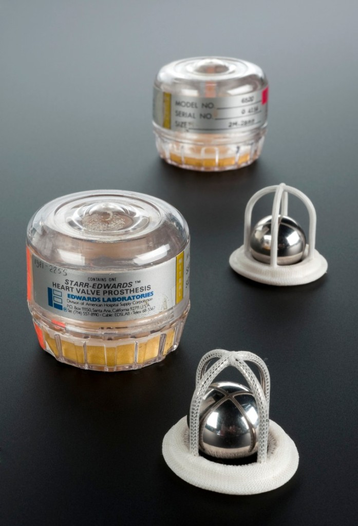 "On a table sit two clear containers with labels reading, ""Starr-Edwards heart valve prosthesis, Edwards Laboratories."" The valves sit on the table - four-legged, open-sided domes of metal covered in mesh-like fabric. Inside each dome sits a close-fitting metal ball/ballbearing."