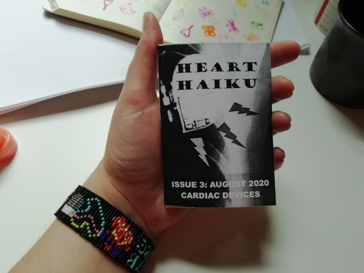 "A hand holds a miniature zine entitled ""Heart Haiku Issue 3: August 2020 - Cardiac Devices"". The owner of the hand is wearing a beaded bracelet featuring an anatomical heart with a three-lead cardiac device attached. There is desk clutter in the background."