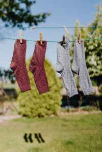 Two pairs of socks attached to an outdoor washing line with clothes pegs.