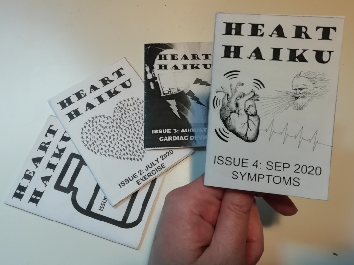 """A hand holds a miniature black and white zine. Cover reads """"Heart Haiku, Issue 4: Sep 2020, Symptoms"""" and shows an image of a bearded male head blowing air onto a vibrating heart with a heartbeat trace line coming out of it."""