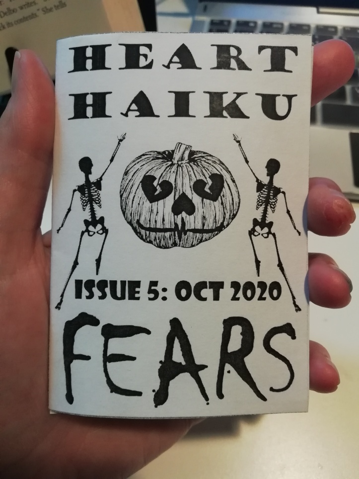 "A hand holds a mini folded zine printed in black and white. Cover has a clipart style image of two skeleton silhouettes presenting a carved pumpkin with hearts for eyes and nose and an ECG reading for a mouth. Text reads: ""Heart Haiku Issue 5: Oct 2020. Fears."""