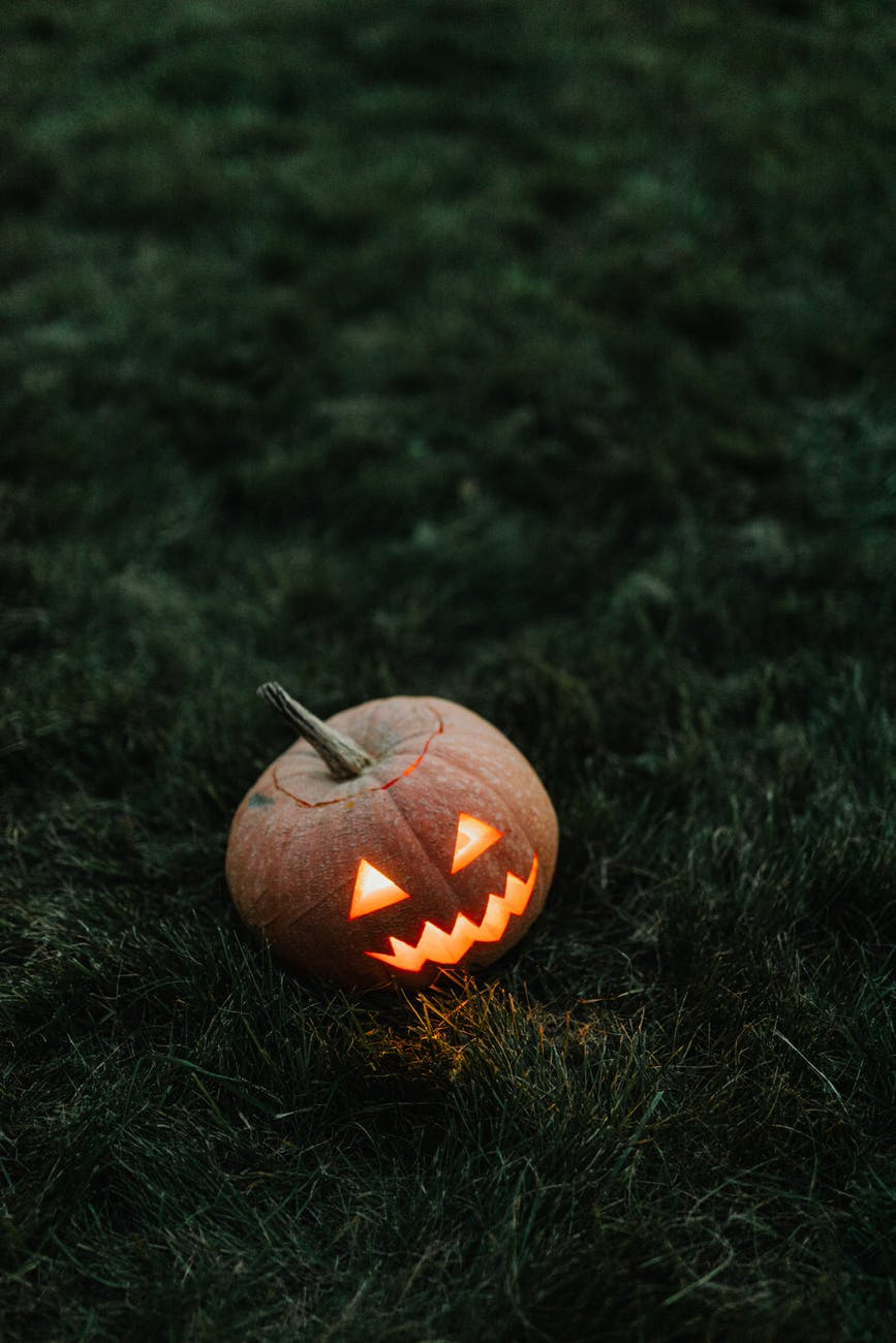 A glowing pumpkin lantern carved with a face sits on the grass