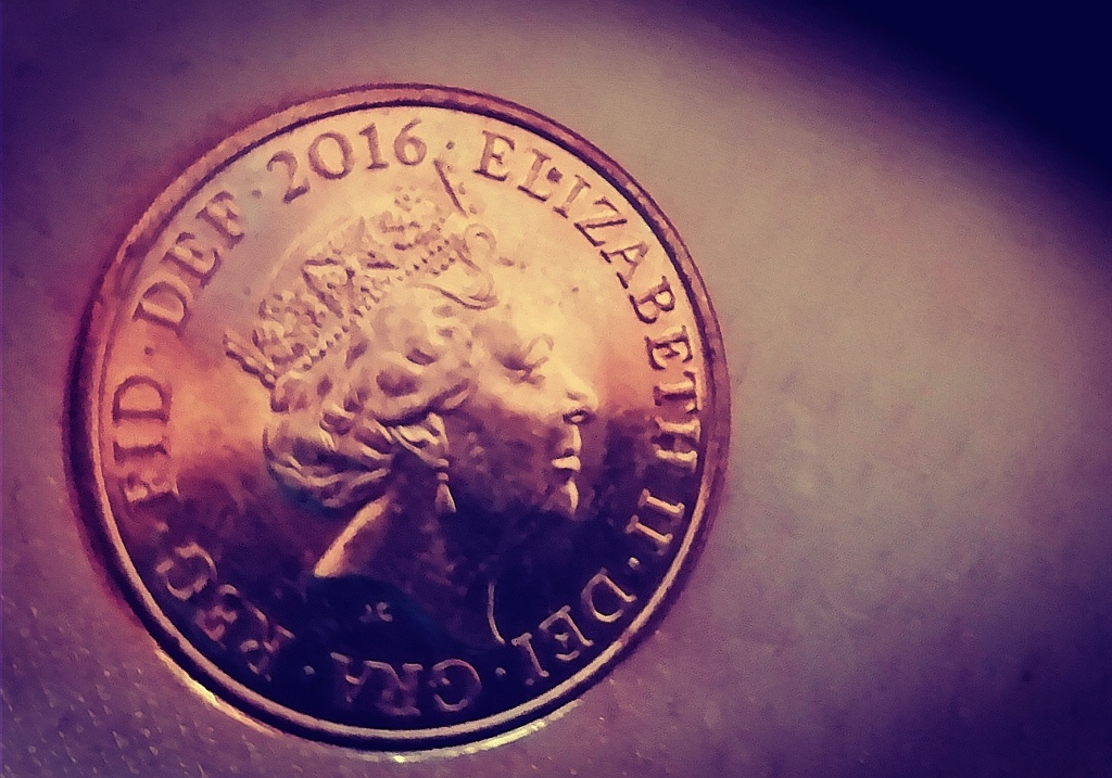 The queen's face on a 1p piece next to a very tiny white scar, approximately 3mm long. The photo has filters applied to make the scar more visible.