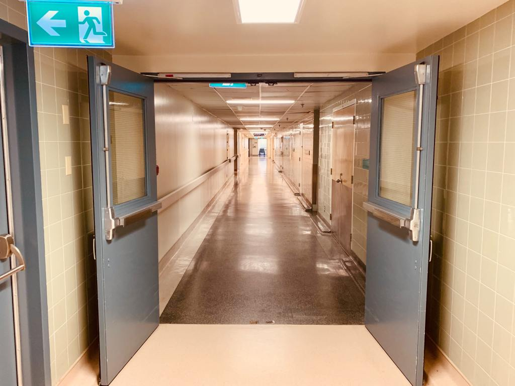 A long corridor in shades of grey, white and pale blue. There is artificial lighting which reflects off the polished linoleum floors, and in the foreground fire doors are propped open. There is an emergency exit sign illuminated and pointing to the left.