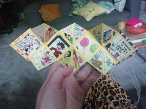 Hand holding a small, open explosion book made from yellow card with pictures from a Beano annual stuck on the square- and triangle-shaped pages. In the background some mess of family life is visible.