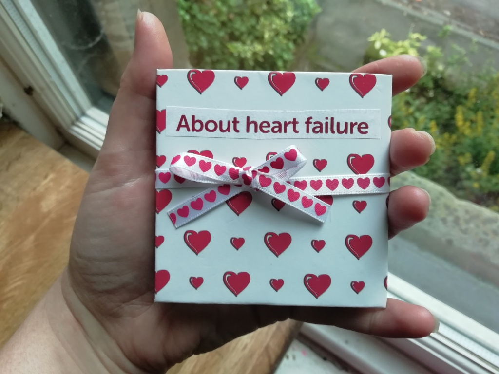 """A hand holds a cardboard square approximately 8cm across. The square is covered in white paper with cartoon-style red love-hearts. Across the centre is a white ribbon with red hearts, tied in a bow. A title (cut from paper, with red text on a white background) reads """"About heart failure."""""""