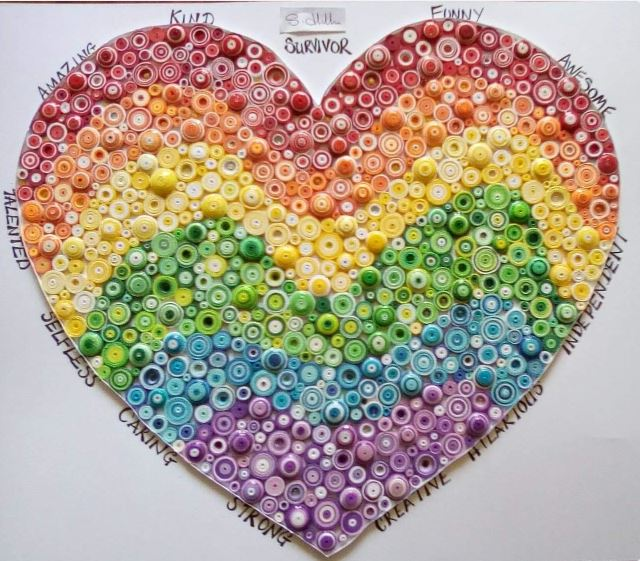 Closely packed beads (arranged in a rainbow pattern, starting from red at the top) fill a simple heart shape against a white background. Hand-written around the edge of the heart are the following words: survivor, funny, awesome, independent, hilarious, creative, strong, caring, selfless, talented, amazing, kind.