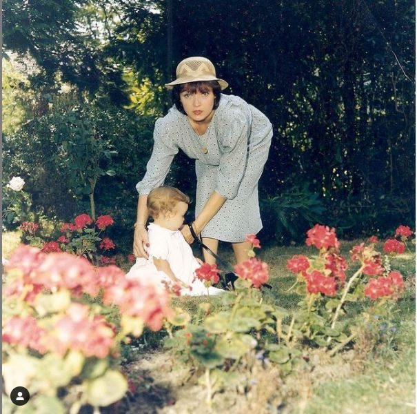 A photo from the 1980s, showing a woman in a floral dress and straw hat bending over a baby who sits on the grass in a white smock-style dress. There are red flowers (geraniums?) in the foreground and trees and bushes behind. It looks like a summer's day at a family event.