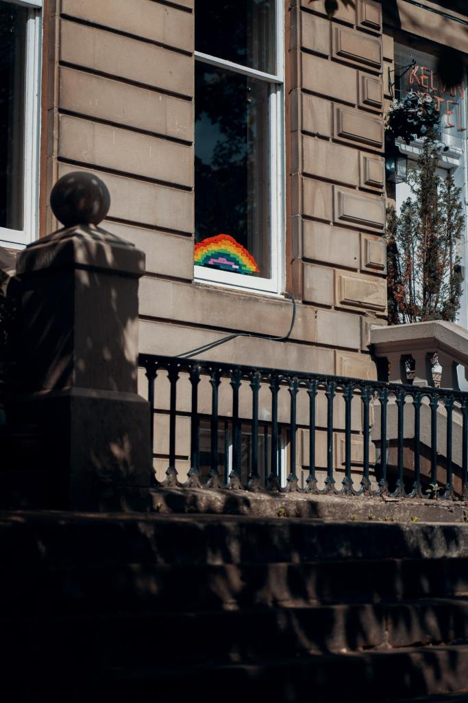 Photograph of a Glasgow tenement building with a rainbow (possibly made of Lego) displayed prominently in a window.