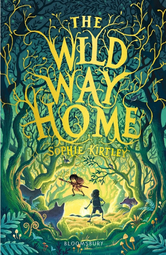 Book Cover: The Wild Way Home by Sophie Kirtley, published by Bloomsbury. Cover illustration shows two boys standing in a wild-looking forest clearing. The boy facing the viewer looks to be wearing animal skins and holds a spear. He is hunched defensively. Facing him, with his back to the viewer, is a boy in modern-day shorts and T-shirt. He has no weapon but also stands defensively. Watching the standoff from the trees are three wolves.
